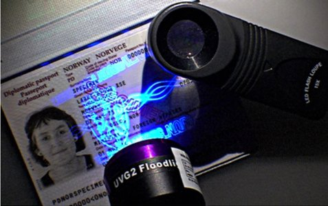 Lommelykt med UV-lys brukes på personaliaside i Norsk pass (specimen).. UV-trykket på siden lyser opp.