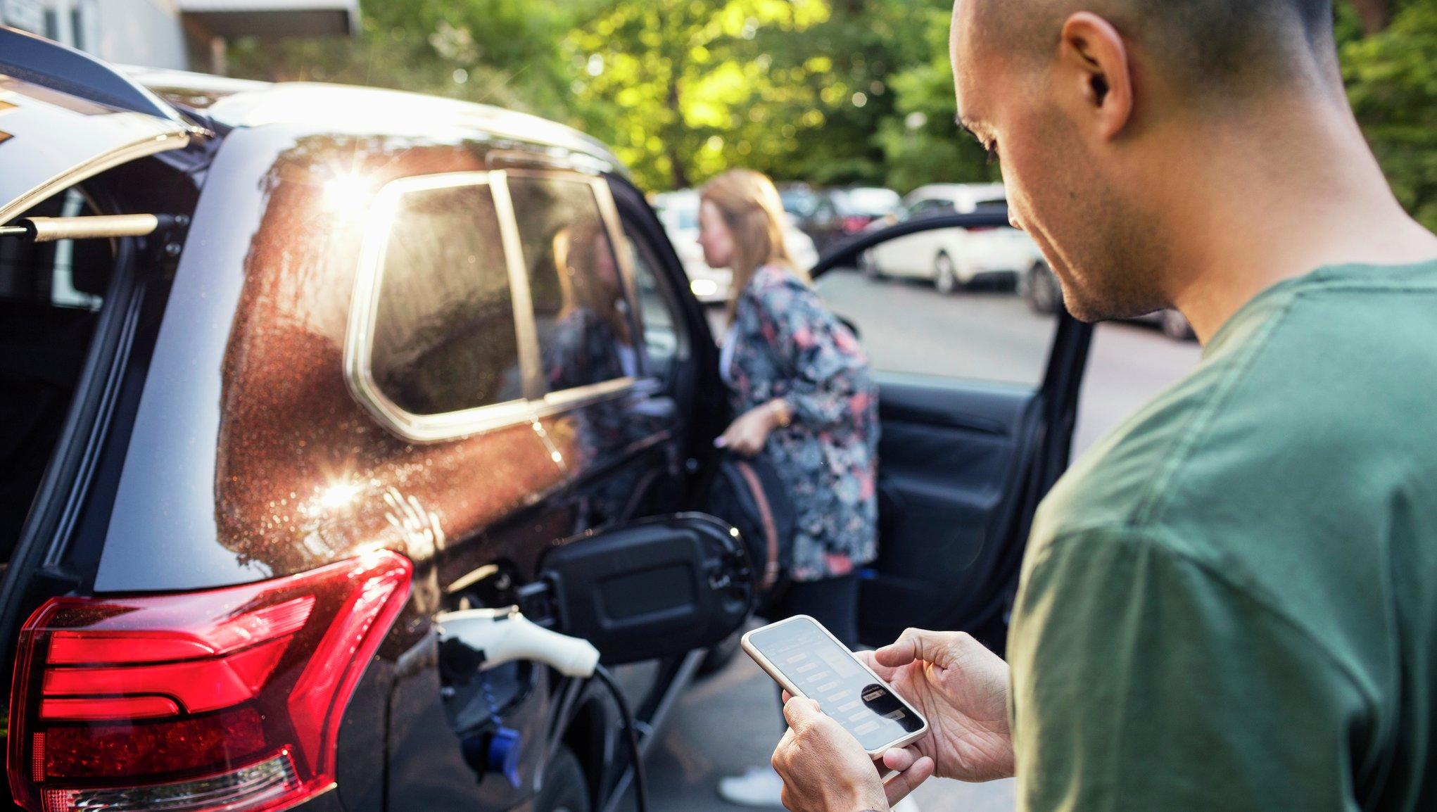 Mies käyttää älypuhelinta, taustalla auto latauksessa ja nainen