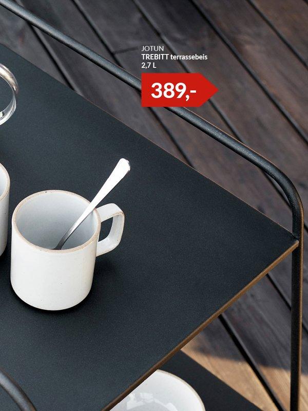 To stk hvite kopper på bord ute på mørkebrun terrasse