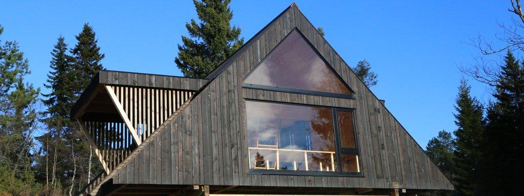 Dagsturhytta på Leikanger ein fin haustdag i oktober. Hytta er svart og trekanta med store vindauge mot fjorden.