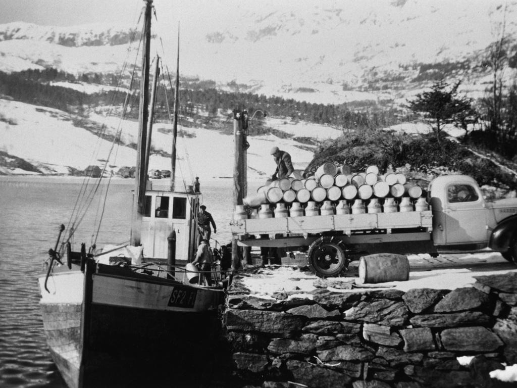 Gamalt svart-kvitt-foto av mjølkebåten som gjekk til Bygstad meieri tidlegare. Det står ein laste bil fullasta med mjølkespann på kaien, og tre mann er i ferd med å lasta spanna over på båten.