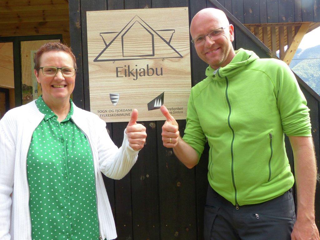 Karen Marie Hjelmeseter og Atle Skrede ved opninga av dagsturhytta Eikjabu i Luster. Dei smiler og gjev tommel opp framfor skiltet på hytta.