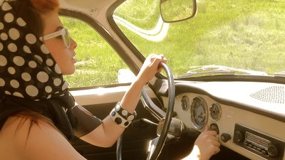 Nainen vanhan auton kyydissä