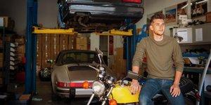 Mies autokorjaamossa moottoripyörän ja kahden käytetyn auton kanssa.