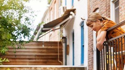 En kvinna ser ut genom balkongen