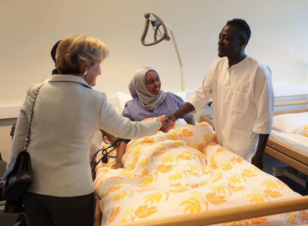 Dronning Sonja handhelser på elev ved helsefag på Firda vidaregåande skule, dei står i undervisningsrom ved ei sjukehusseng der det ligg ein elev, to andre elevar står også ved senga.