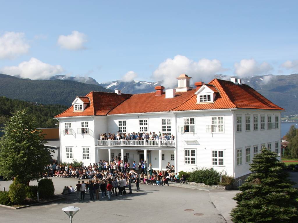 Foto som syner den gamle Firda gymnas-bygningen ved Firda vidaregåane skule. På skuleplassen og på balkongen i andre etasje er det samla mange elevar. Det er sol og blå himmel.