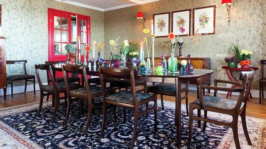 GULLSTUE: Alle rom har sin karakter. I spisestuen er veggene kledd med gulltapet med fugler på grønne grener. Den røde døren mot kjøkkenet har farge fra innebygde vitrineskap på motsatt vegg. Bordpynt, tepper og møbler er gjenbruk og kommer fra fjern og nær. (Farge dør, S 1580-Y90R)
