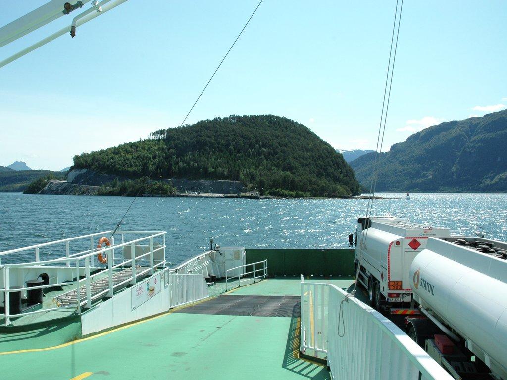 Foto teke frå hengedekket frå ei ferje som er på veg over Nordfjorden ein solskinsdag.