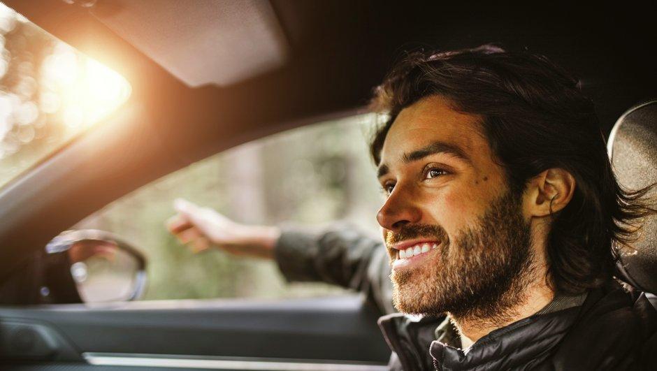 Ruskeahiuksinen mies ajaa autoa hymyillen