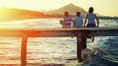Nainen ja kaksi poikaa laiturilla lomailemassa