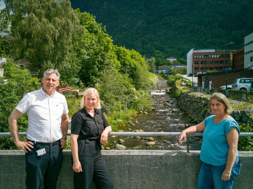 Tre personar står på brua ved elvi utanfor Fylkeshuset i sola.