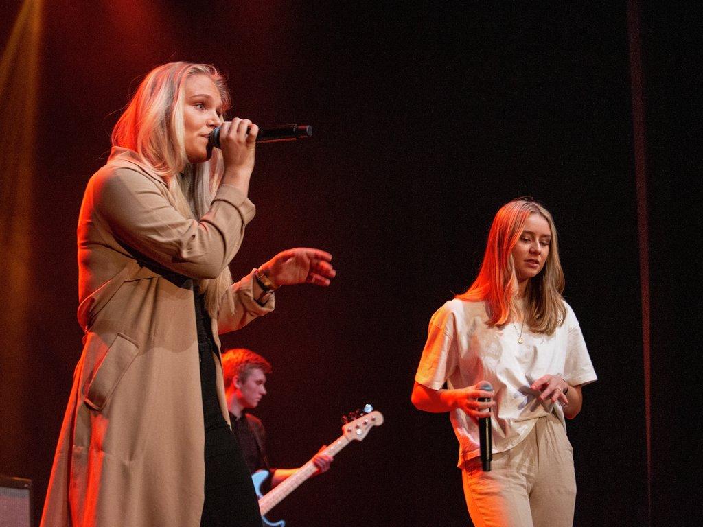 Foto av to jenter som syng på ei scene.