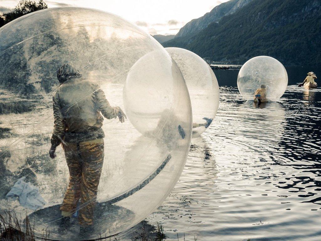 Foto frå teaterfestivalen i Fjaler 2017. Biletet syner fleire personar som bevegar seg oppå fjorden i store, blanke ballar.
