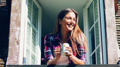 kvinnor med kaffekopp tittar ut från takkupa