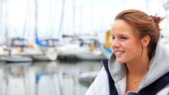Nuori nainen satamassa, purjeveneitä taustalla