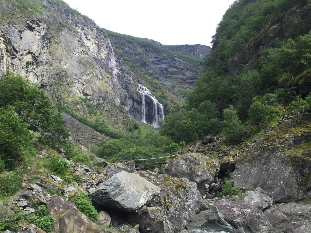 Foto frå Aurlandsdalen. Biletet syner store steinar i framgrunnen, ei hengebru og ein foss litt lenger oppe i dalen.