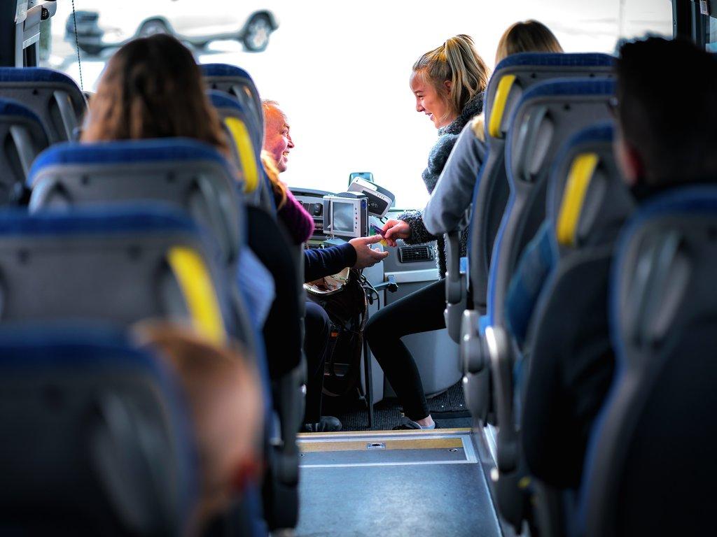 Ungdom som betalar for seg på buss