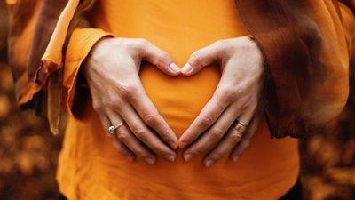 Raskaana olevan kädet vatsalla sydämen muodossa