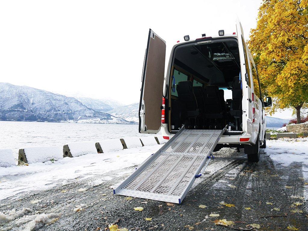 Foto av stor drosje, maxitaxi, som har bakdørene opne. Det er lagt på plass ein rampe for rullestol ut bakdørene.