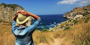 Nainen katsoo merta etelän lomakohteessa