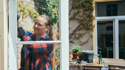 Nainen poraa ruuveja ikkunaan