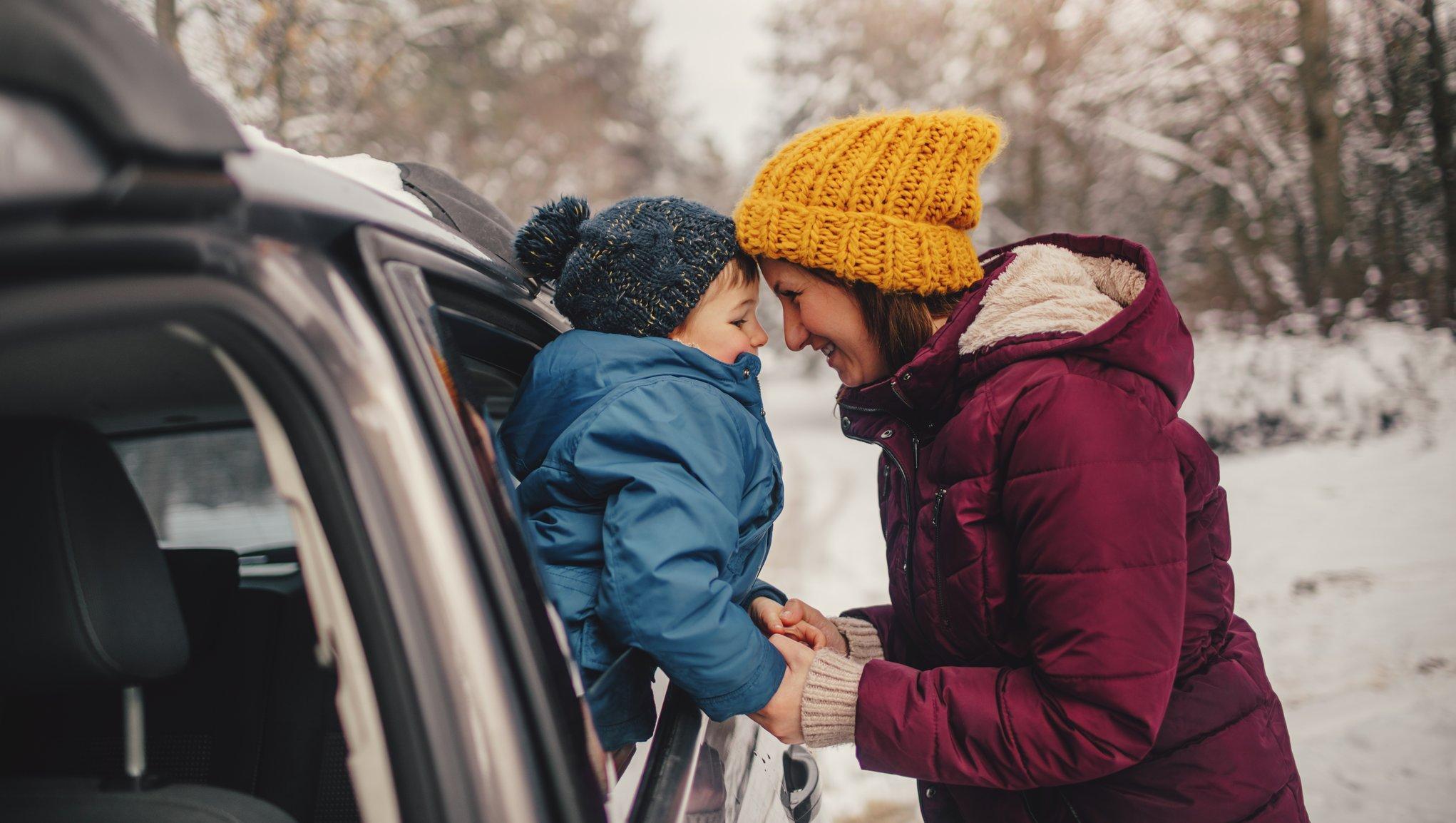 mamma och barn vid bil