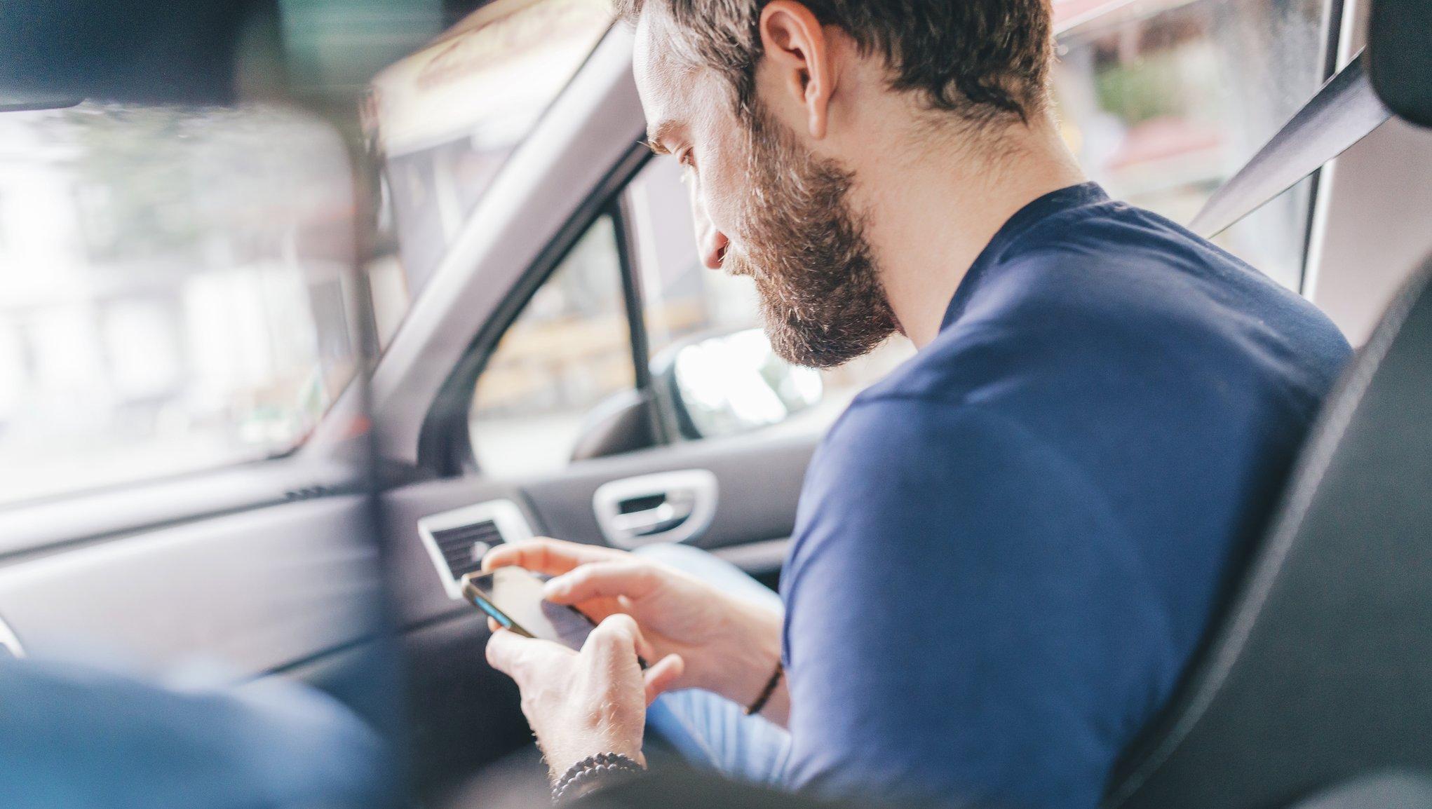 Mann ser på mobilen mens han sitter i bil