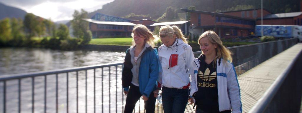 Foto av tre unge jenter på ei bru i Førde. Dei er kledde i jeans og tynne jakkar. I bakgrunnen ser vi Hafstad vidaregåande skule.
