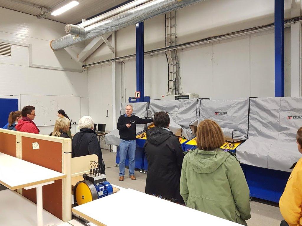 Ei rekkje personar står i ein hall og høyrer på ein mann som viser fram og fortel om maskinar i ei verksemd. Frå næringsreisa i Føre 2018.