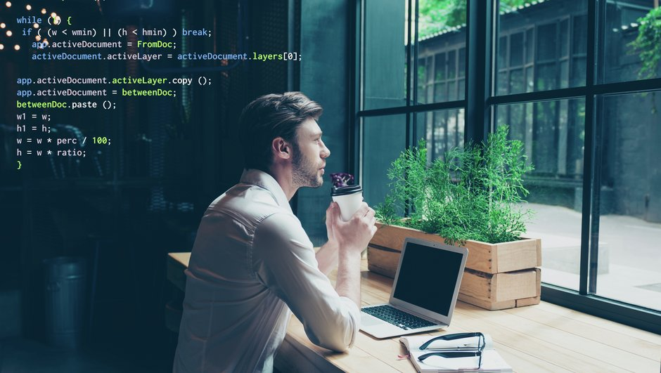 man sitting with computer. html code in the background.