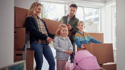 Perhe kantaa muuttolaatikoita