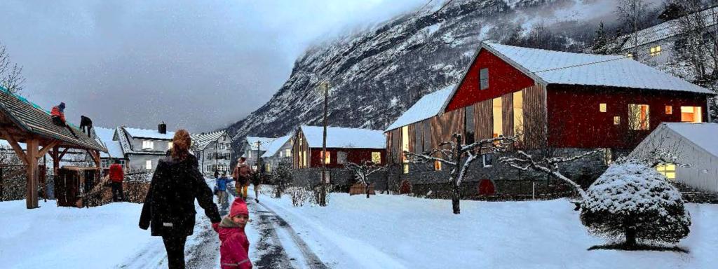 Illustrasjon frå eit byggjefelt i Stryn med snødekt veg, fjell i bakgrunnen og barn og vaksne som går på vegen.
