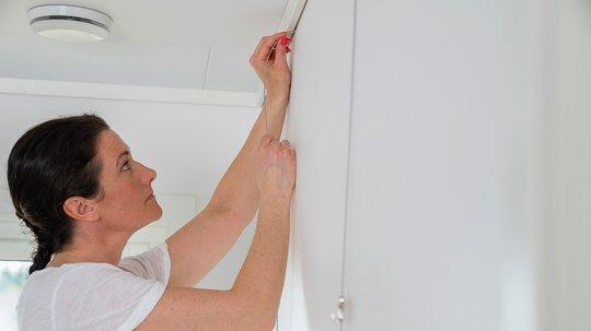 Opphenget hukes på plass i taklisten helt uten bruk av verktøy. Vil du flytte opphenget til høyre eller venstre, skyver du det på plass. Vil du flytte opphengt til en annen vegg, tar du det ut og huker det på plass der du vil ha det. Foto: Rindalslist.