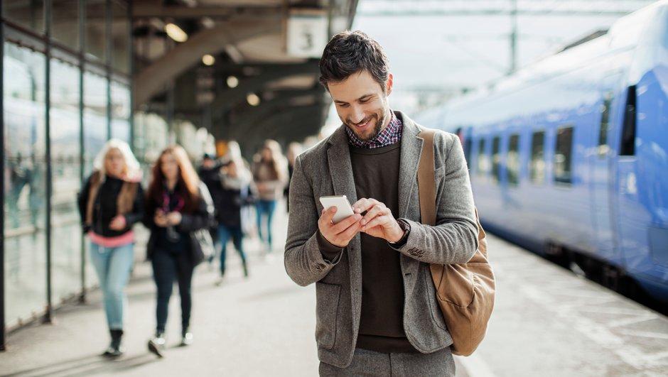 Mies selaa älypuhelina juna-aseman laiturilla.