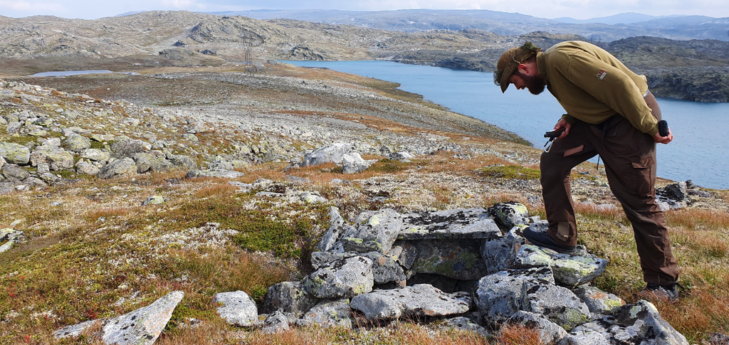 Foto av person som studerer ei fangstgrav på Aurlandsfjellet