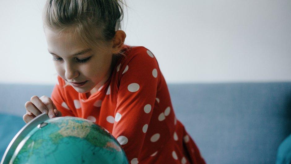 Tyttö tarkkailee karttapalloa.