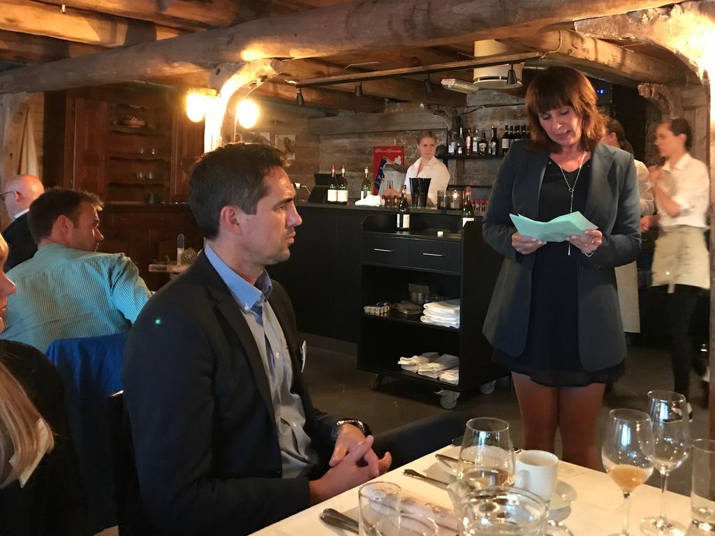 Foto av fylkesordførar Jenny Følling som held tale ved ein festmiddag. Ho er kledd i svart kjole og held notatar. Vi ser fleire som sit ved borda.