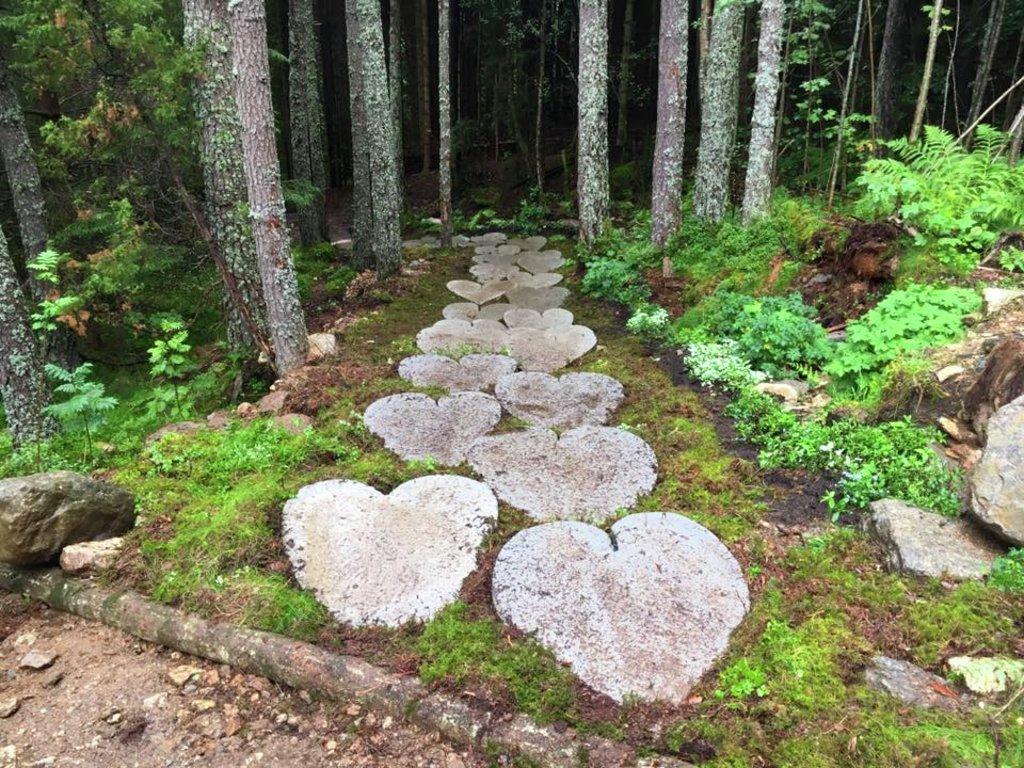 Foto frå hjartestien i Trivselsskogen på Sandane. Det er lagt ned steinheller med hjarteform på stien gjennom skogen.