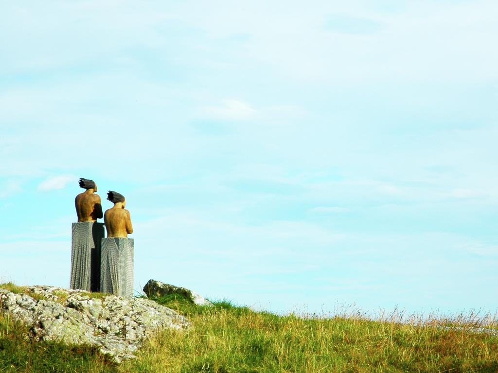 Foto av statuen av to kvinneskikkelsar som står og skodar utover. Vi ser statuane, grønt gras i framgrunnen og ein blå, litt skyete himmel i bakgrunnen.