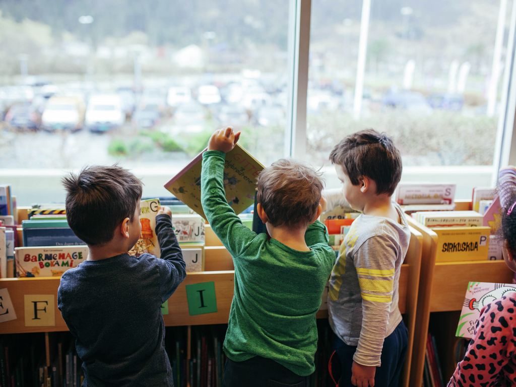 Fire barn leiter etter bøker i ein kasse med barnebøker