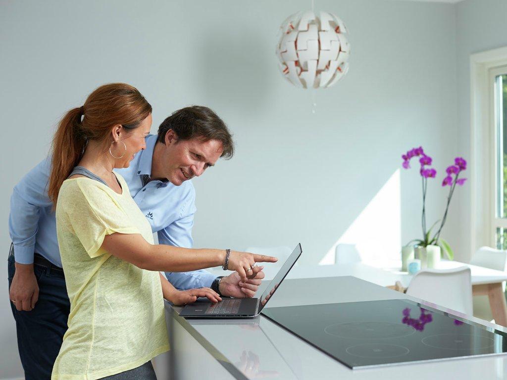 Foto av ei kvinne og ein mann som står ved kjøkendisken og ser og peiker på skjermen på ein bærbar pc. Dei smiler.