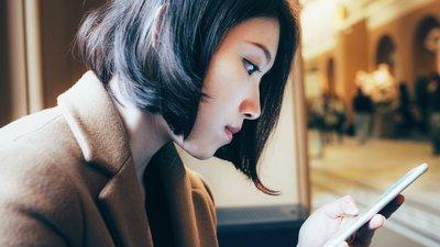 ung tjej läser på mobil