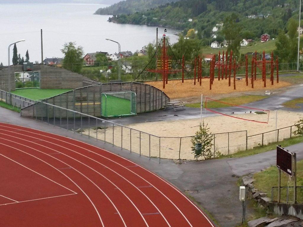 Idrettsanlegg med ballbinge og utsikt mot fjord og skog.