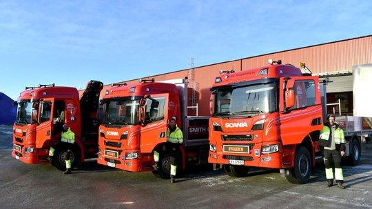 Byggern røde lastebiler og sjåfører klare for levering