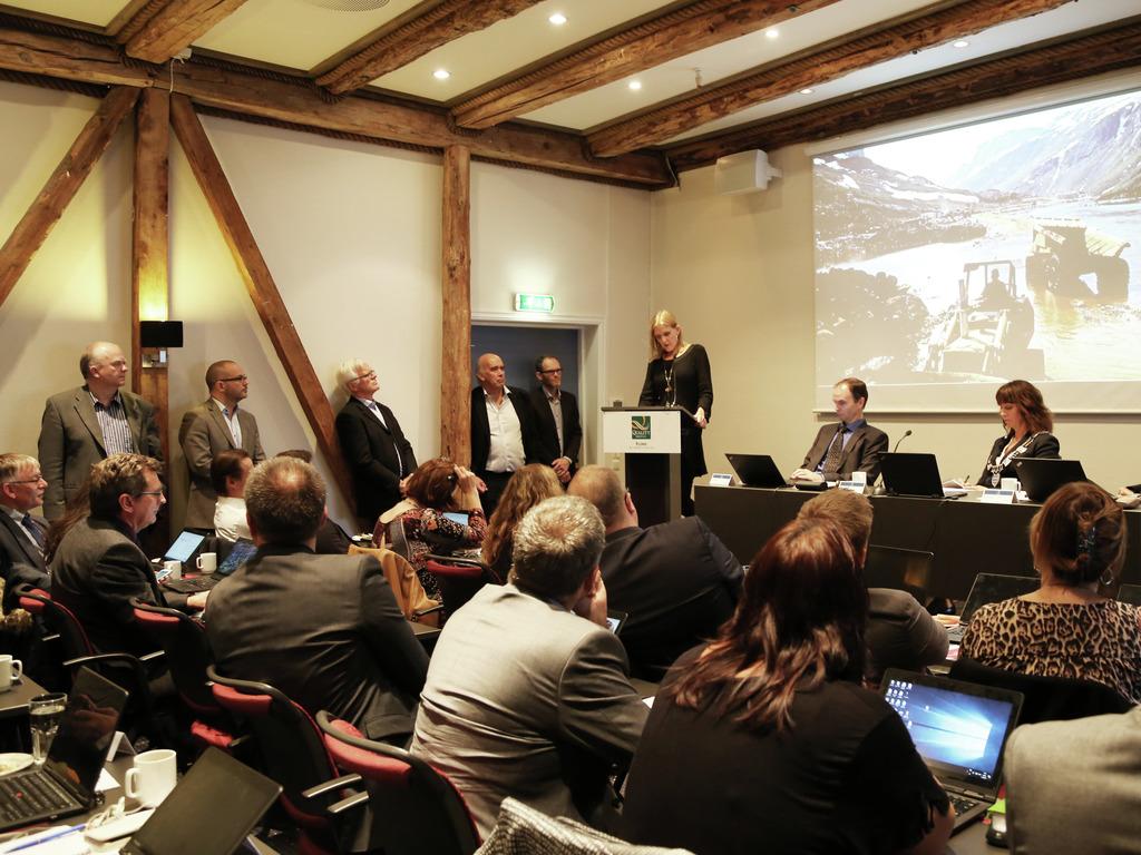 Foto frå presentasjonen av fylkessoga for fylkestinget. Ein av forfattarane Hege Roll-Hansen står på talarstolen, medan dei andre forfattarane står langs veggen.