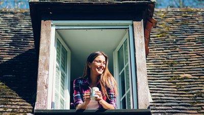 Nainen katsoo talon ikkunasta ulos