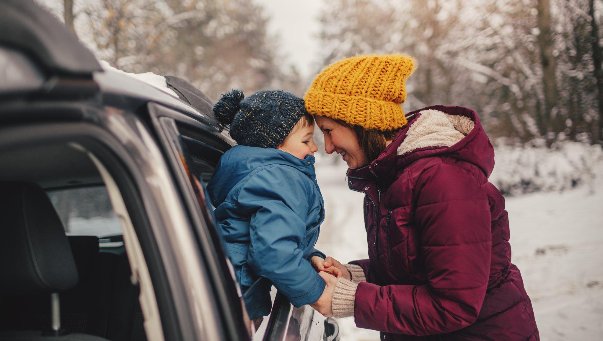 Lapsi ja äiti auton ulkopuolella talvella
