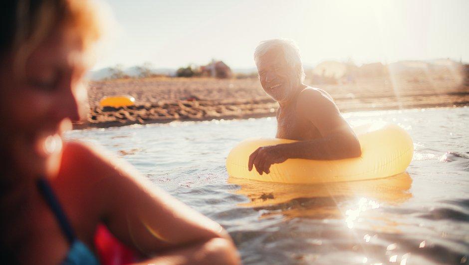 Ikääntyneempi nainen ja mies vedessä uimarannalla