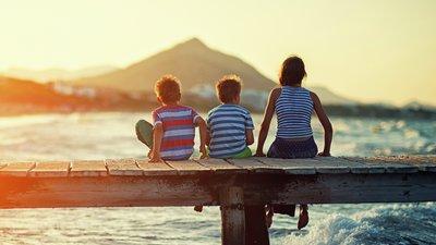 Familj på bryggan i solnedgång